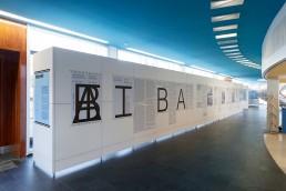 der Innenraum der Ausstellung, mit einem langen blockartigen weißen Aufsteller, auf dem