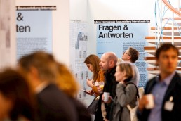 Besucherinnen und Besucher der Ausstellung schauen sich die Aufsteller und Wandplakate an