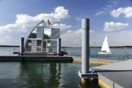 ein kleines Segelboot auf dem Wasser und ein Bungalow, der von der Form her an ein Segelboot erinnern soll