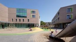 Kinder spielen in großen Sandflächen und auf einer Rutsche im Hof des Bildungszentrums