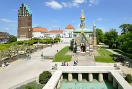 Menschen spazieren im sonnigen Park, im Vordergrund eine üppig verzierte kleine Kirche, im Hintergrund die große Halle mit dem Turm