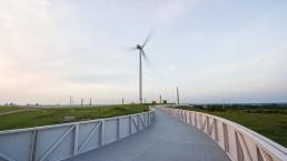 ein breiter Steg mit Geländer führt über den grünen Hügel