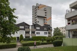 eine Fußgängerin vor Mehrfamilienhäusern mit ordentlich gestutzten Hecken und einem Hochhaus