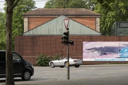 eine Straße mit Autos vor der Rückwand eines Gebäudes