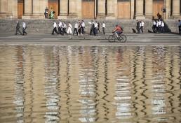 hinter einer Wasserfläche geht eine Gruppe von Menschen in Anzügen an einer Treppenanlage vorbei