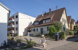 zwei Mädchen gehen in einer vorstädtischen Straße auf dem Gehweg vor Ein- und Mehrfamilienhäusern