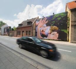 ein Auto fährt auf der Straße an einer Plakatwand vorbei, die zwei gemalte Jungen zeigt, einer davon mit verbundenen Augen