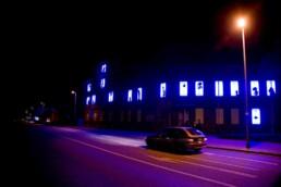 farblich verfremdeter Blick auf ein Gebäude mit beleuchteten Fenstern, in denen Figuren als Schattenspiel zu sehen sind