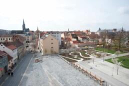 Blick von oben auf historische Gebäude, einen Platz und eine Gartenanlage