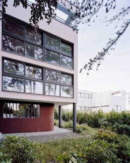 ein heutiger Blick auf ein strenges Gebäude mit horizontalen Fensterbändern, das auf Stützen steht