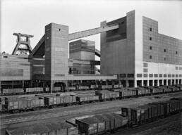 historisches Schwarz-Weiß-Foto mit offenen Eisenbahnwaggons, die Kohle geladen haben, vor dem Zechenwerk