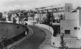 Blick von weitem auf die gesamte Siedlung mit einer Straße davor