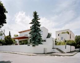 zwei weiße Villen stehen in Gärten, die von weißen Mauern eingefasst sind
