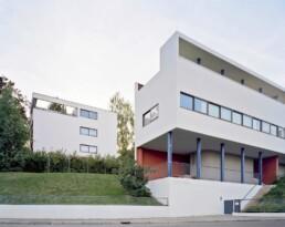 zwei moderne weiße, streng geometrische Gebäude in unterschiedlichen Formen stehen an einem Hang