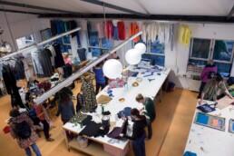 Blick von oben einen Raum, in dem mehrere Menschen mit Stoffen arbeiten
