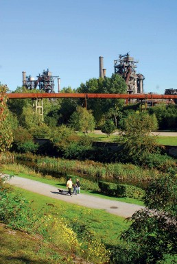 eine kleine Familie geht durch eine grüne Parkanlage, im Hintergrund die großen Industriestrukturen