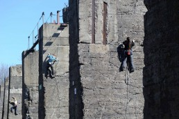 drei junge Menschen klettern angeseilt an riesigen Betonstrukturen hoch