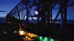 das große Stahlgerüst ist farbig beleuchtet, vor einem leuchtend blauen Nachthimmel