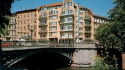 im Vordergrund ein Kanal mit einer historischen Brücke, im Hintergrund ein großes Eckgebäude einer Blockrandbebauung mit geschwungenen Balkonen und Erkern