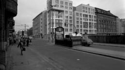 im Vordergrund eine Straße und ein U-Bahn-Aufgang, im Hintergrund ein Eckgebäude mit gerasterter Fassade und ohne Dachaufbau