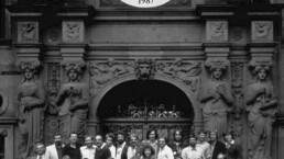 eine große Gruppe von Menschen steht, sitzt und liegt für die Fotografie vor einem opulent dekorierten Altbauportal