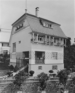 eine Villa mit ornamentalen Fassadenverzierungen und einem Satteldach steht in einem Garten