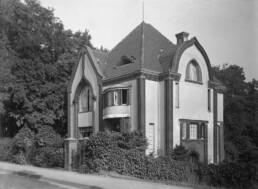 eine Villa mit organisch geschwungenen Giebeln steht in einem Garten