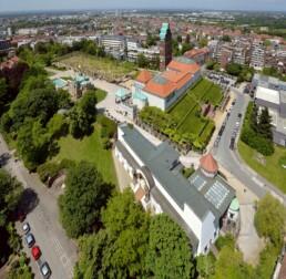 Luftaufnahme auf das Ensemble der Mathildenhöhe, im Hintergrund die Stadt