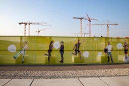 "On the construction site fence ""Faces of the Seestadt"" residents present their activities in the IBA area © Wien 3420 / Rimshot Fotografie"