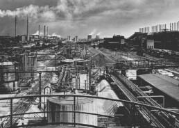 historisches Schwarz-Weiß-Foto über eine große industrielle Anlage mit Tanks und vielen Rohren, im Hintergrund rauchende Schlote