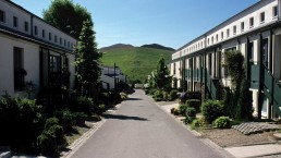 eine kleine Wohnstraße führt auf einen grünen Hügel, links und rechts helle Reihenhäuser mit Vorgärten
