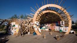 in einer runden, offenen Holzkonstruktion hängen großformatige, von Kindern gemalte Bilder