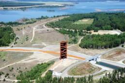 Luftbild mit großen Brachflächen, Baumgruppen, Gewässern im Hintergrund, im Zentrum der Stahlturm