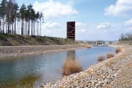 über den mit Schottersteinen eingefassten Kanal blickt man von Weitem auf einen skulpturalen, eckigen Turm aus rostfarbenem Stahl