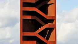 der skulpturale Turm mit Einblick in die offenen Treppenstrukturen im Inneren, oben stehen Menschen und blicken in die Landschaft