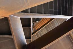Blick von oben in den skulpturalen Aufgang, dessen Treppen kreuz und quer verlaufen