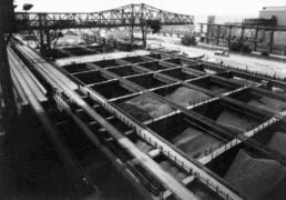 historisches Schwarz-Weiß-Foto von Gruben, in den verschiedene Materialien lagern