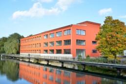 ein ehemaliges, nun saniertes Fabrikgebäude in einem kräftigen Orangeton direkt an einem Kanal