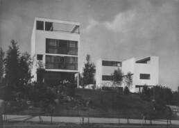 hinter einem leicht aufsteigenden Garten ragen zwei moderne, kubische Wohngebäude in den Himmel