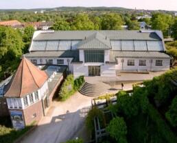 eine große Halle mit gestaffelter Dachstruktur steht in einer grünen Landschaft