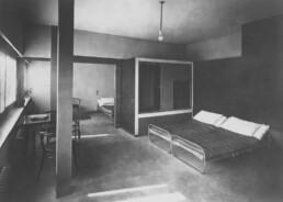 zwei Betten mit Metallgestellen stehen vor einem großen eckigen Kleiderschrank, am Fenster steht ein Tisch mit zwei Stühlen aus geschwungenem Holz
