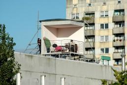 in einer offenen Installation auf einem Dach wird eine Wohnsituation simuliert, drei Menschen nutzen den Raum