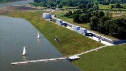 """an einem See mit flach absteigendem grünen Ufer steht eine Reihe von Pavillons mit der Aufschrift """"see"""""""