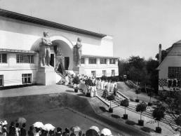 Menschen in weißen Gewändern stehen vor einem weißen Gebäude mit einem Runden Portal, das von zwei riesigen Steinfiguren eingefasst wird, im Vordergrund Publikum mit Zylindern und weißen Sonnenschirmen